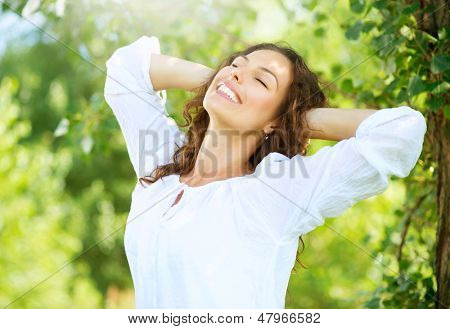 Beautiful Young Woman Outdoor. Enjoy Nature. Healthy Smiling Girl in the Park