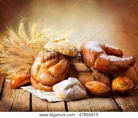 Bakery Bread on a Wooden Table. Various Bread and Sheaf of Wheat Ears Still-life.