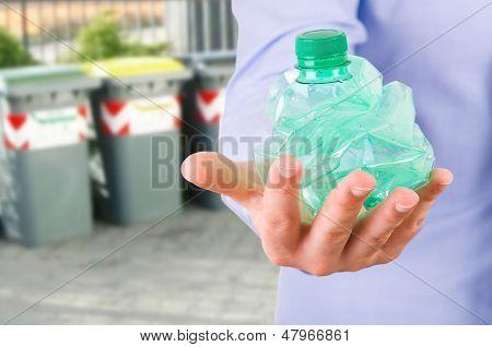 Businessman holding a crushed bottle.