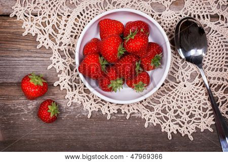 A bowl of fresh ripe strawberries on lace tablecloth and rustic wood table. Vintage effect with intentional vignetting