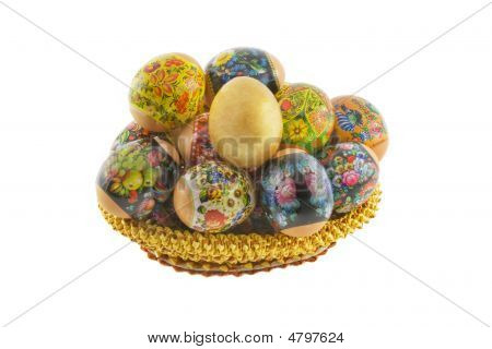 Many Easter Decorated Eggs Lying In A Basket Weaved From Straw Isolated Over White Background
