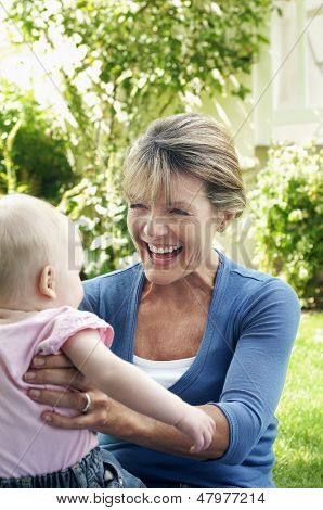 Cheerful middle aged grandmother playing with granddaughter in the garden