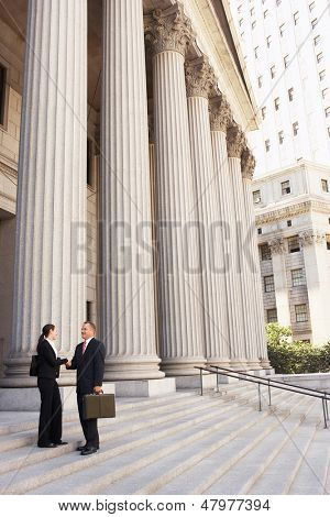 Full length side view of male and female attorneys shaking hands on courthouse steps