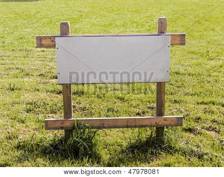 "on a lawn is a sign ""building for house for sale"". construction site for a new home."