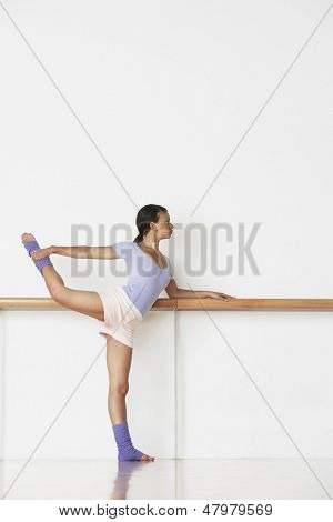 Full length of young ballerina practicing at bar in rehearsal room