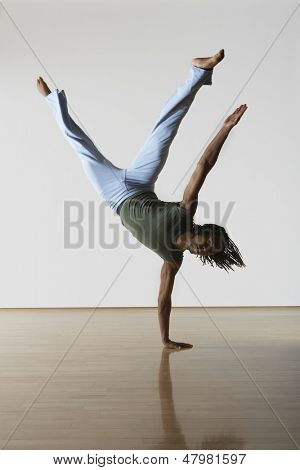 Young male dancer standing on one hand in rehearsal room