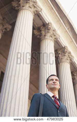 Low angle view of a serious male lawyer outside courthouse