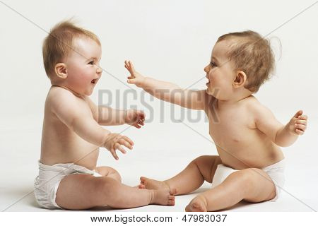 Side view of two babies playing on white background