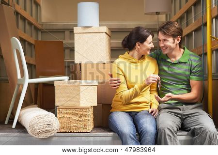 Smiling young couple holding home key while sitting back of moving van
