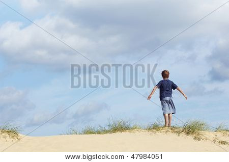 Rear view of a young boy standing on sand dune in wind with arms outstretched