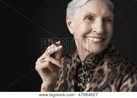 Closeup of an elegant senior woman smoking cigarillo against black background