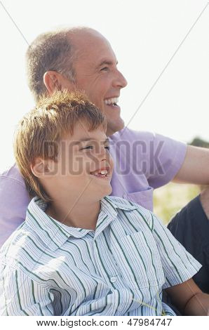 Side view of a happy father and son sitting at on beach