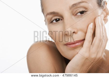 Closeup of relaxed middle aged woman with hand on chin over white background