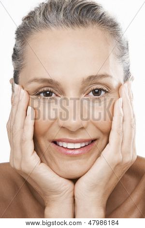 Closeup portrait of happy middle aged woman with hands on face over white background