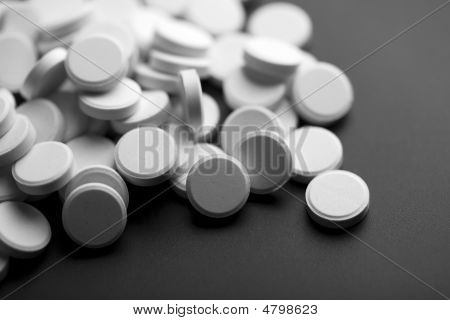 White Pills Over Black Background