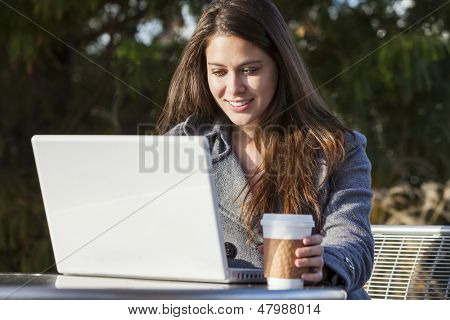 A young woman or girl student using a laptop outside and drinking takeaway coffee