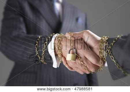 Midsection of two businessmen shaking hands wrapped in gold chain and padlock against gray background