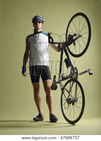 Full length of a bicyclist standing alongside bicycle against colored background