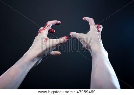 Grey skin bloody zombie hands, studio shot over gray background
