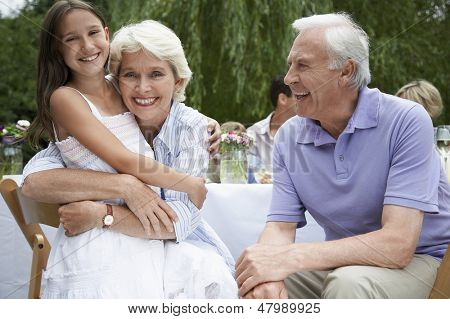 Portrait of happy grandparents with granddaughter sitting at table in garden