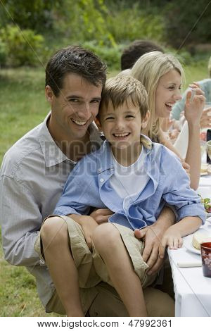 Portrait of son sitting on father's lap while dining with family in garden