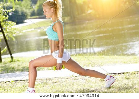 fitness instructor exercising with small weights in green park