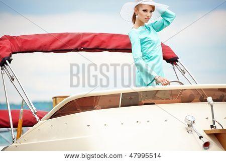 Elegant retro woman wear  dress , sitting near the wooden yacht. 60's inspiration