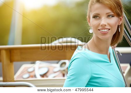 Elegant retro woman wear  dress , sitting near the wooden yacht. 60's inspiration