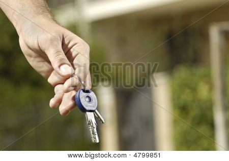 Young Man And New Home, Looking Building With Door Key In Hand;