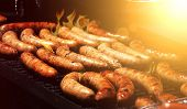 stock photo of sausage  - sausages on the barbeque grill with flames and sunlight - JPG