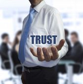 pic of trustworthiness  - Sophisticated businessman holding the word trust in front of a business team - JPG