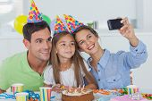 Woman taking pictures of her family during her daughter birthday party