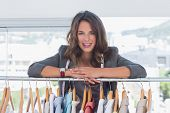 stock photo of blazer  - Fashion designer leaning on clothes and smiling to the camera - JPG