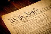 stock photo of patriot  - The Constitution of the United States of America on a wooden desk - JPG
