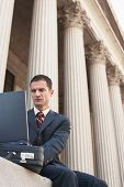 stock photo of crew cut  - Low angle view of a male lawyer using laptop outside courthouse - JPG