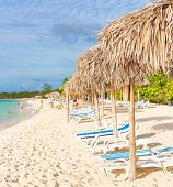 image of coco  - Umbrellas and out of focus people at a beach in Cayo Coco  - JPG