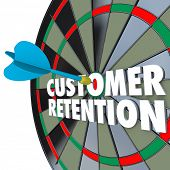 image of customer relationship management  - The words Customer Retention on a dartboard with a dart hitting a perfect bull - JPG