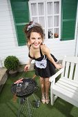 foto of brazier  - Young beautiful housemaid fry sausage on brazier near white house - JPG