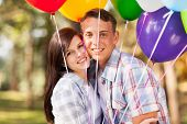 smiling romantic teen couple outdoors with helium balloons
