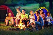 foto of tent  - group of happy kids roasting marshmallows on campfire - JPG