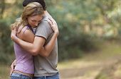 stock photo of intimacy  - Side view of a couple standing on forest trail and hugging - JPG