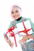 stock photo of fitri  - Happy young muslim woman with gift boxes isolated over white background - JPG