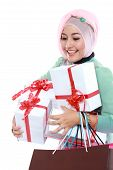 stock photo of fitri  - Happy young muslim woman with shopping bag and gift boxes isolated over white background - JPG