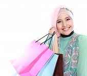stock photo of fitri  - Closed up of happy young muslim woman with shopping bag isolated over white background - JPG
