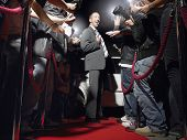 pic of limousine  - Excited man on red carpet by limousine posing in front of paparazzi - JPG
