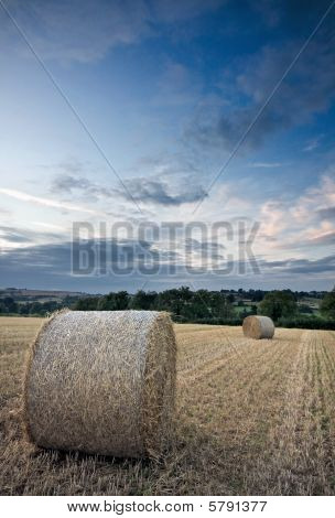 Harvested Straw Bales Under A Sunset Sky