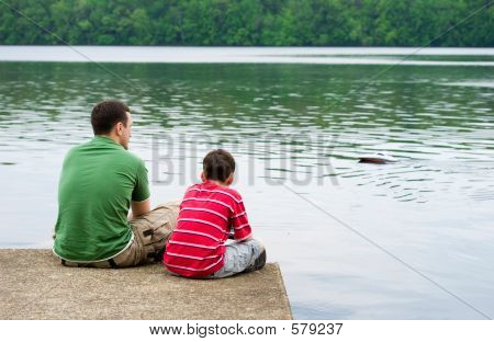 Father and son talking and playing with a remote controlled boat