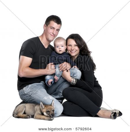 Portrait Of Young Family With Baby Boy And 2 Month Year Old Wolf Cub Studio Shot