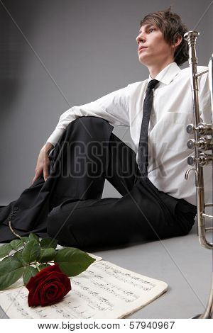Young man with trumpet and red rose