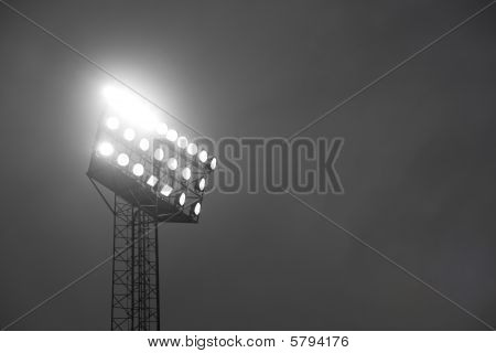 Stadium spotlights lit at night.
